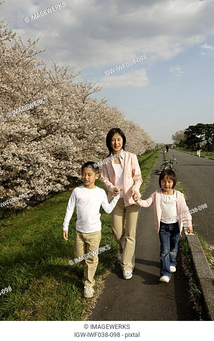 View of a mother and children walking on pathway