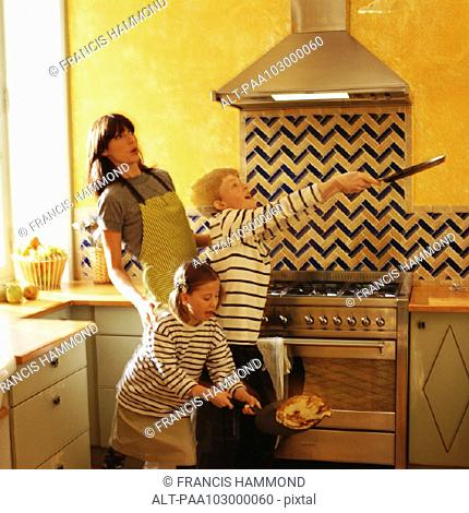 Children and mother standing in front of oven, children flipping crepes, blurred motion
