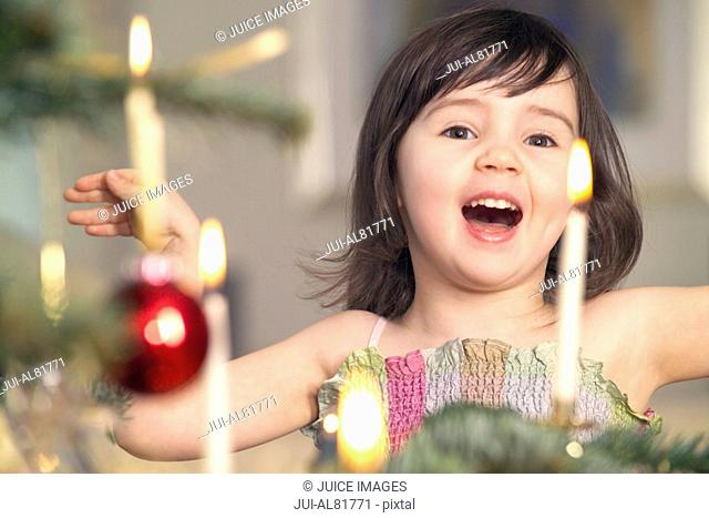 Young girl singing next to Christmas tree