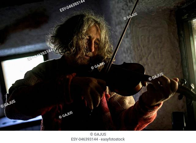 Elderly male musician with tousled long hair playing a classical violin at home in a head and shoulders portrait of him in a shadowy room with an absorbed...