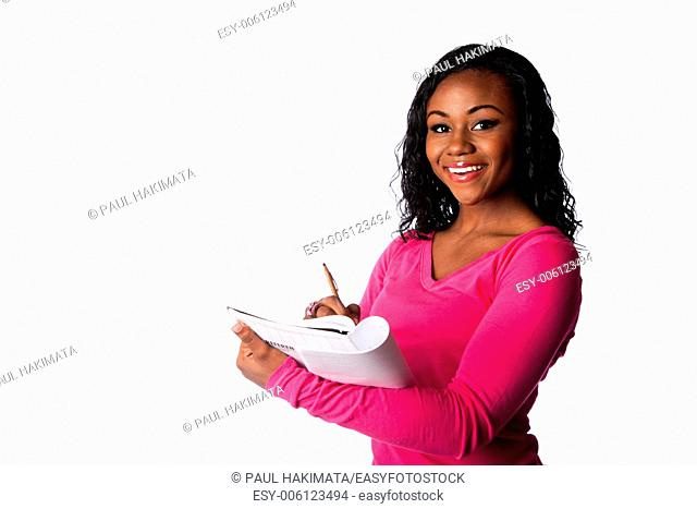 Beautiful happy smart college student smiling and writing in notebook taking notes, isolated