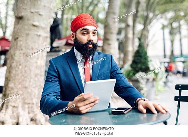 Indian businessman sitting in Manhattan, using digital tablet