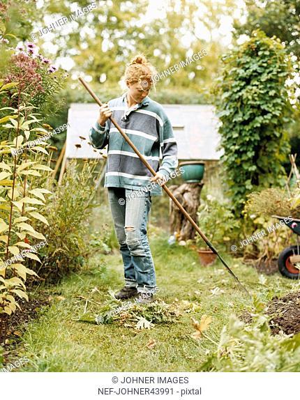 Woman raking leaves in garden