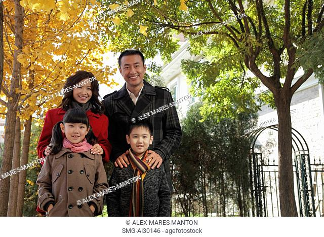 Family of four standing together in front of their house
