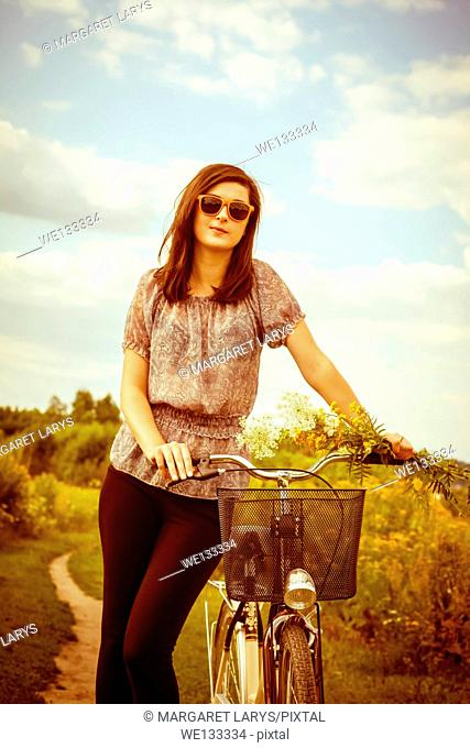 Beautiful young woman and a bike in the summer fields with wildflowers on a sunny summer day