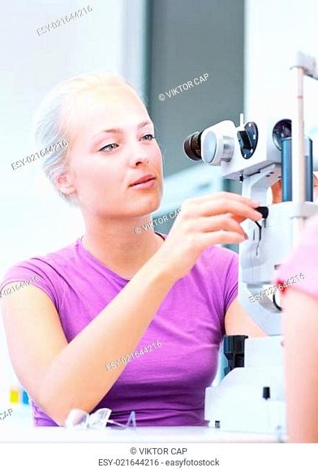 optometry - beautiful young female optometrist examining a patient (color toned