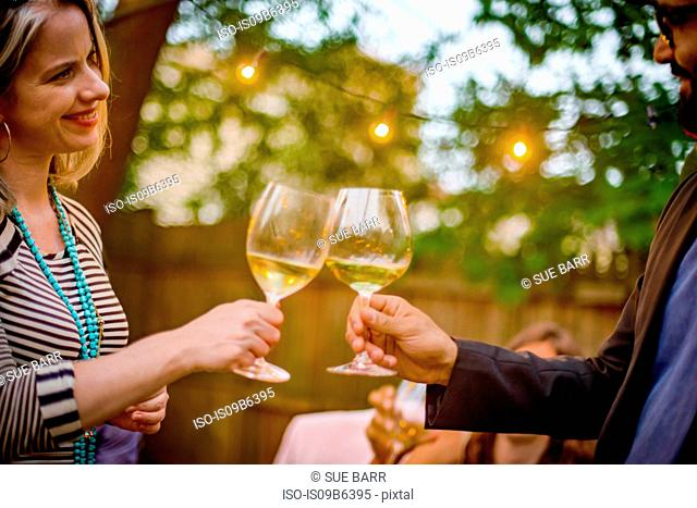 Man and woman at garden party, holding wine glasses, making a toast