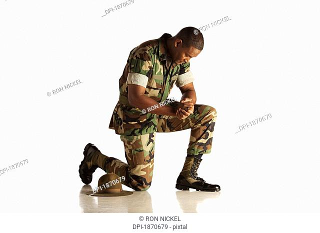 a military man kneeling with his head bowed