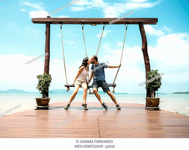 Thailand, Koh Lanta, kissing couple sitting on swings in front of the sea