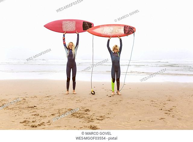 Spain, Aviles, two young surfers on the beach holding their surfboards