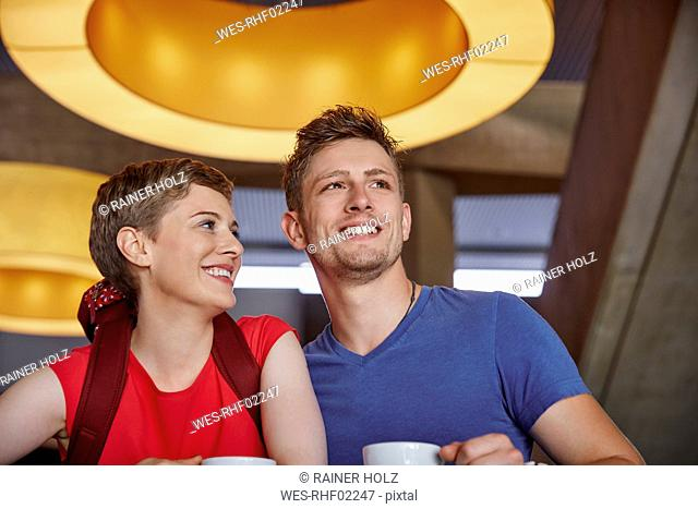 Smiling couple with backpack in a cafe