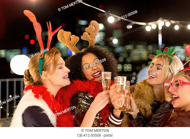 Young women wearing Christmas reindeer antlers and toasting champagne glasses at rooftop party