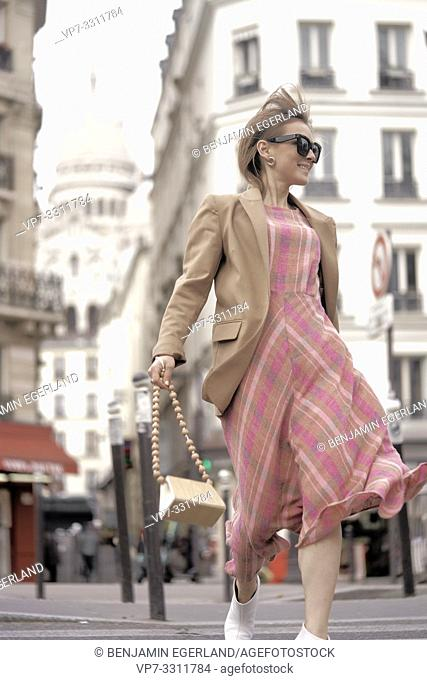 fashionable blogger woman running at street during fashion week, in front of touristic sight Basilica Sacré-Cœur, in city Paris, France