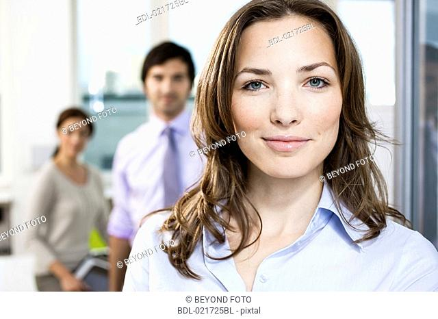 portrait of businesswoman in front of colleagues