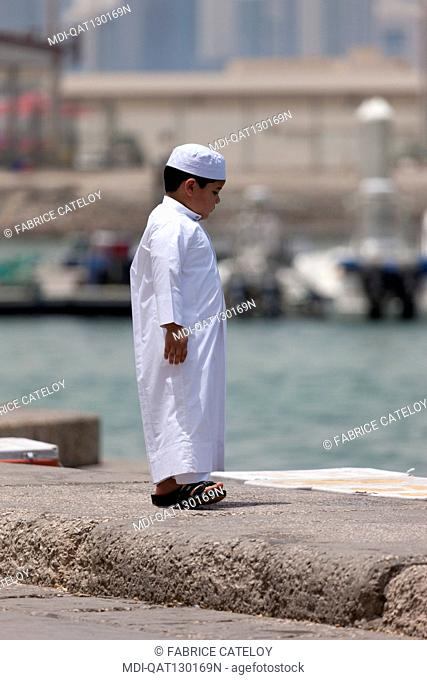 Qatar - Doha - Fish market on the corniche - Young Qatari boy looking fresh fishes into ice boxes