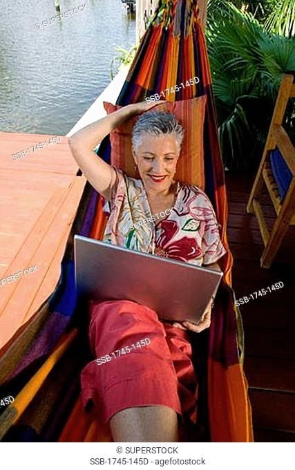 High angle view of a senior woman lying in a hammock and using a laptop