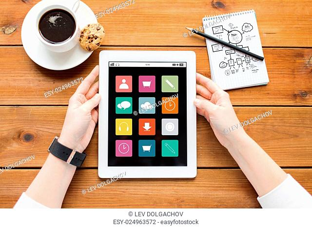 multimedia, business, education, technology and people concept - close up of woman with menu icons on tablet pc computer screen and coffee cup on wooden table