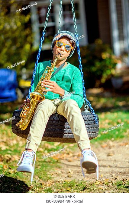 Teenage boy, sitting on tire swing, playing saxophone