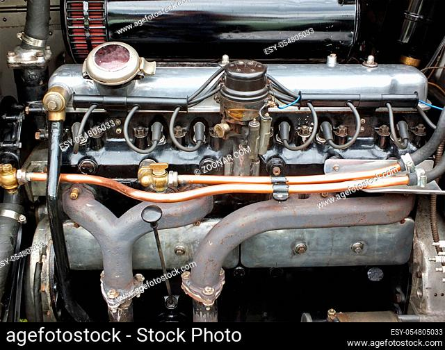 close up of a large vintage six cylinder petrol engine in an old fashioned sports car