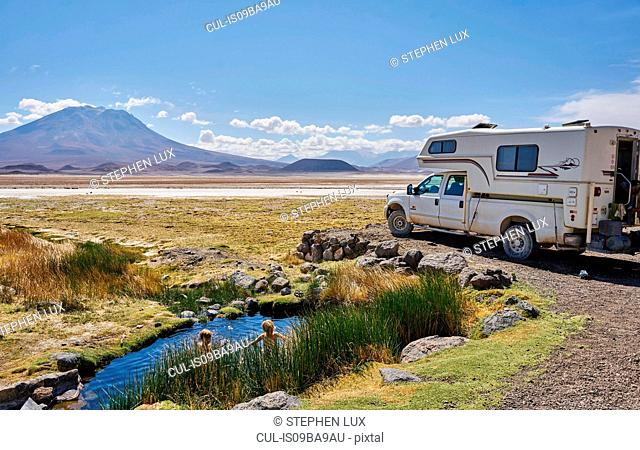 Two boys playing in water pool beside parked recreational vehicle, Salar de Chiguana, Chiguana, Potosi, Bolivia, South America