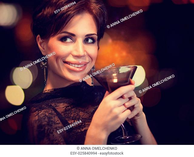 .Portrait of beautiful happy woman drinking tasty alcohol cocktail on blur glowing lights background, with pleasure spending time on luxury night party