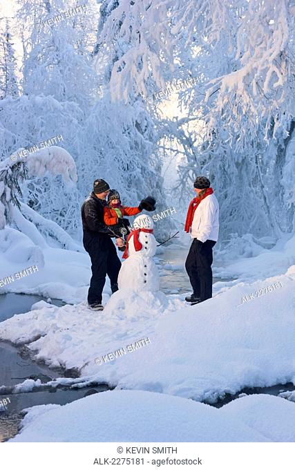 Family putting a top hat on a snowman next to a small stream in a hoarfrost covered forest russian jack springs park anchorage southcentral alaska winter