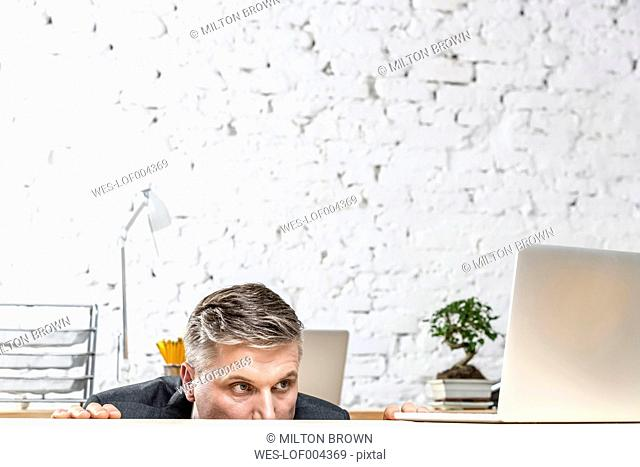 Businessman hiding at desk peeking at laptop