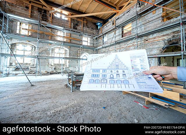 ILLUSTRATION - 15 July 2020, Bavaria, Straubing: A building plan is kept in the burnt-out hall in the historic town hall