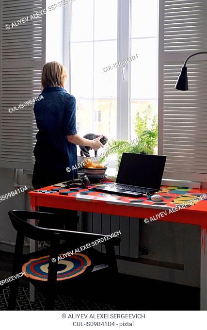 Woman playing with kitten on windowsill