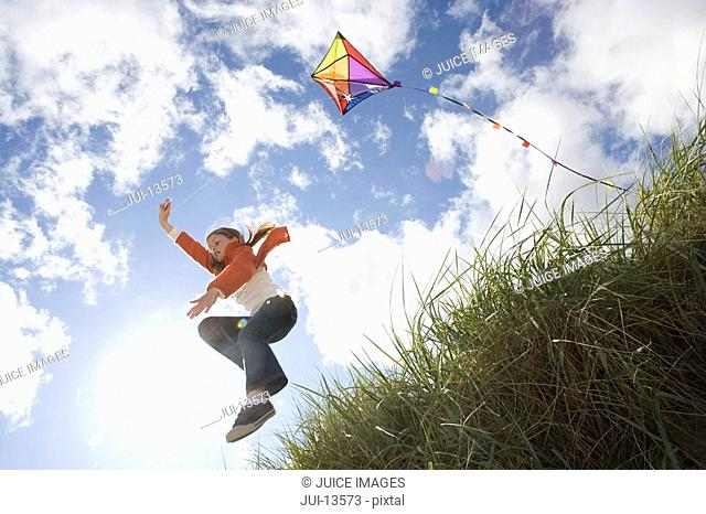 Young girl jumping off hill holding kite