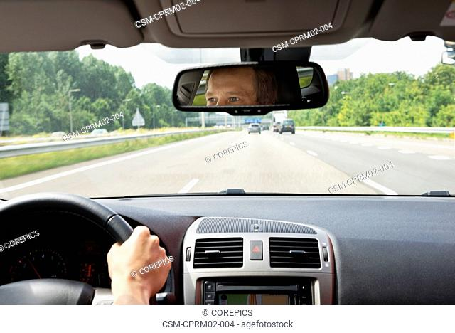 Man, driving a car, with his eyes reflected in the rear view mirror