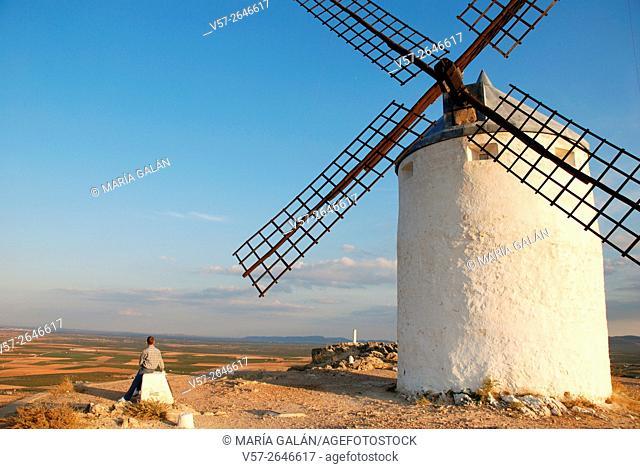 Man looking at the landscape next to a windmill. Consuegra, Toledo province, Castilla La Mancha, Spain
