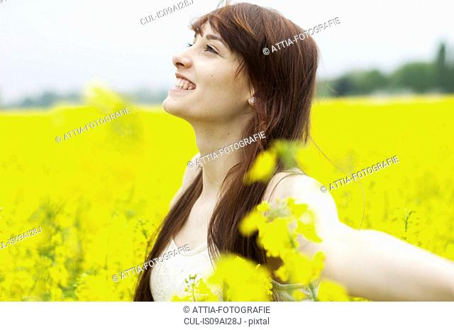 Young woman with arms out in yellow field