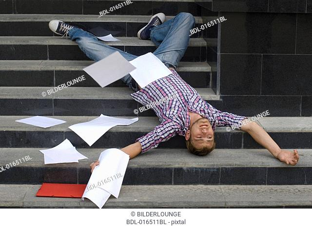young student lying on his back on stairs surrounded by school documents