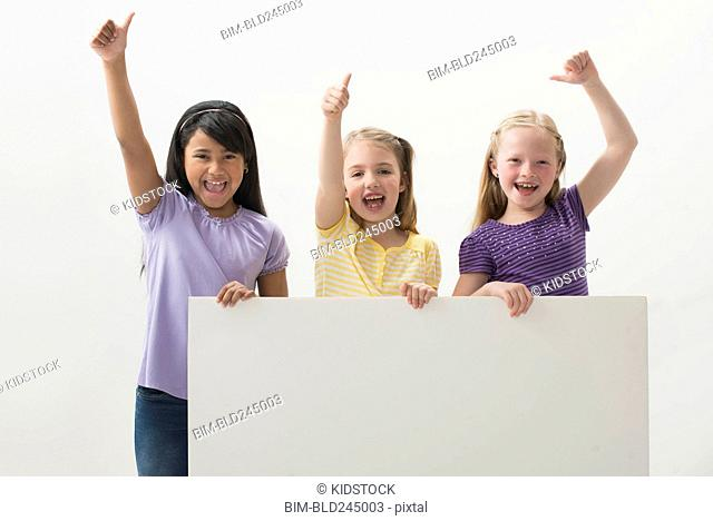 Portrait of smiling girls holding blank placard gesturing thumbs up