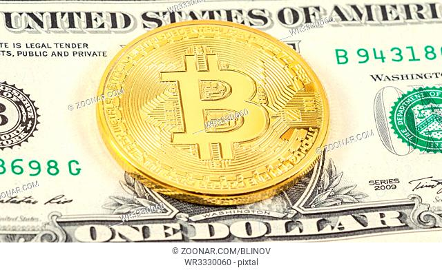 Cryptocurrency of the Bitcoin lying on the american dollar banknote. Business concept of new virtual money