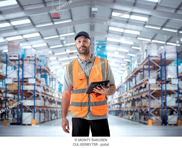 Composite image of warehouse worker with digital tablet