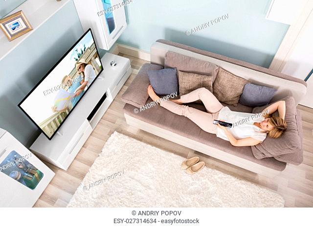 High Angle View Of Woman Lying On Sofa Watching Movies On Television At Home