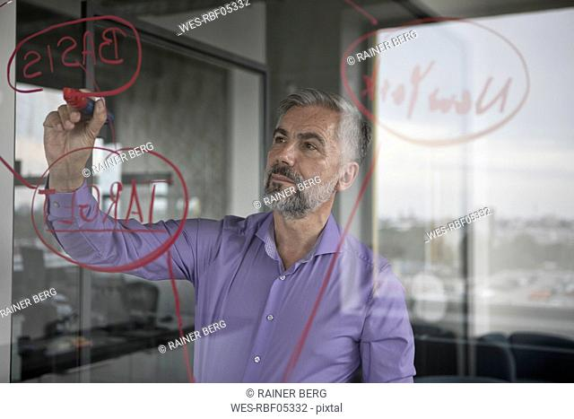 Businessman in office writing on glass wall