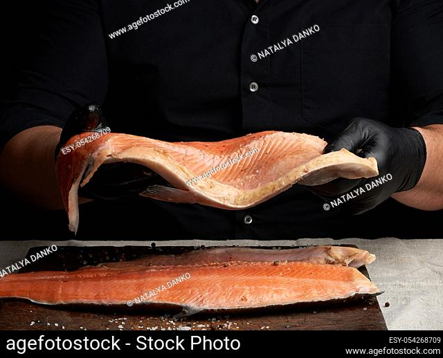 chef in a black shirt and black latex gloves holds a large piece of salmon fish fillet over the table, cooking process, clouse up