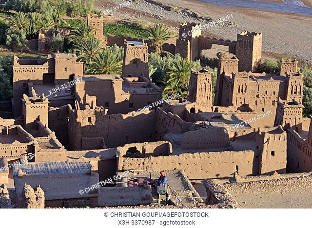 man sitting on the terrace of a cafe overlooking the Ksar of Ait-Ben-Haddou, Ounila River valley, Ouarzazate Province, region of Draa-Tafilalet, Morocco