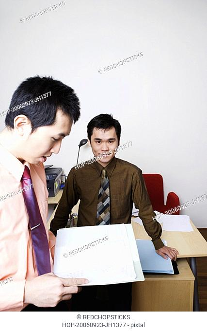 Portrait of a businessman smiling with another businessman reading a file