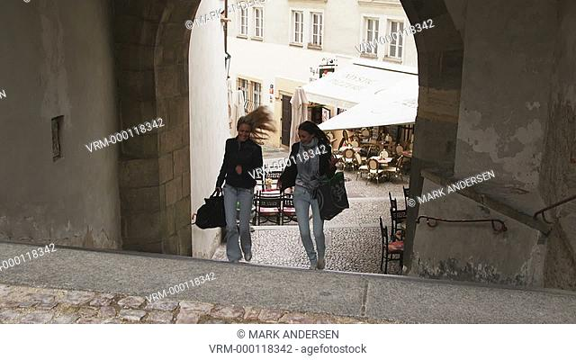 two women running up the stairs on a city street