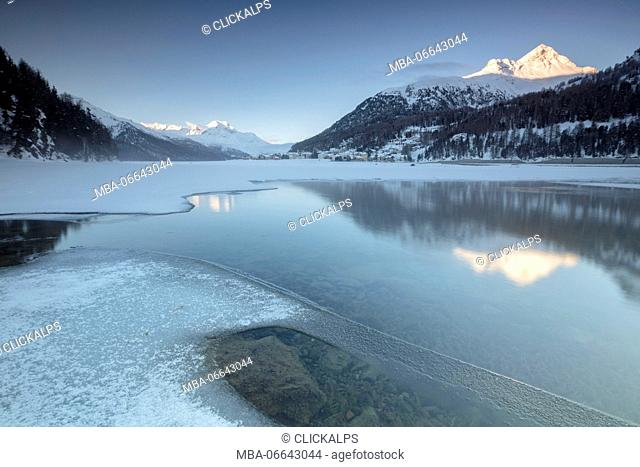 Snowy peaks reflected in the frozen Lake Champfer at dawn St.Moritz Canton of Graubunden Engadine Switzerland Europe
