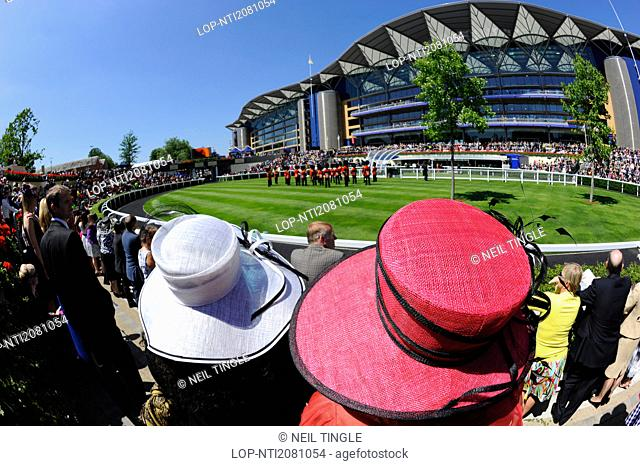 England, Berkshire, Ascot. A large crowd enjoying a performance by a military band in the parade ring on the second day of Royal Ascot 2010