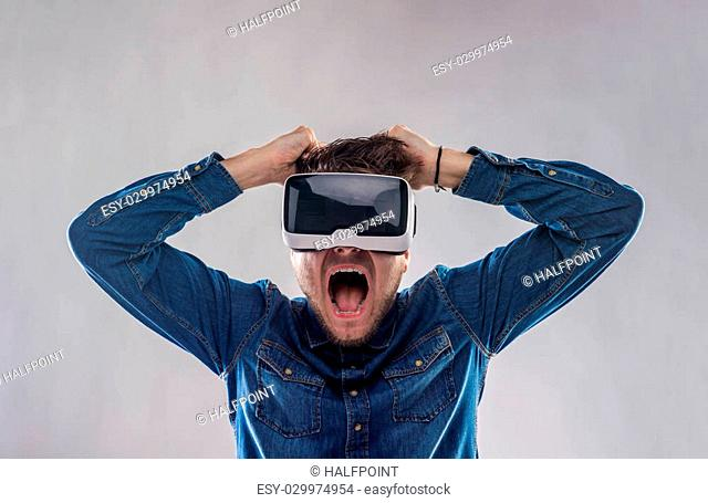 Hipster man in denim shirt wearing virtual reality goggles screaming. Studio shot on gray background