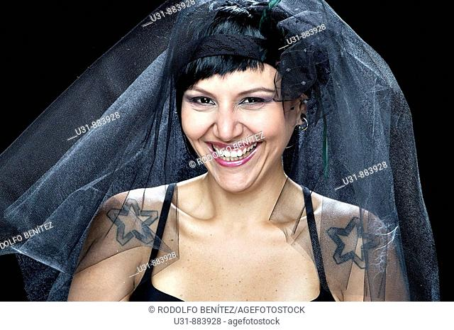 Punk Bride in her late 20s in a studio setting wearing a black wedding dress smiles