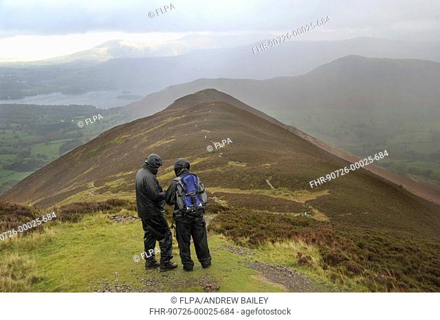 Walkers wearing waterproof clothing, looking at map during rain shower, view from Causey Pike, with distant views of Catbells and Derwentwater, Lake District N