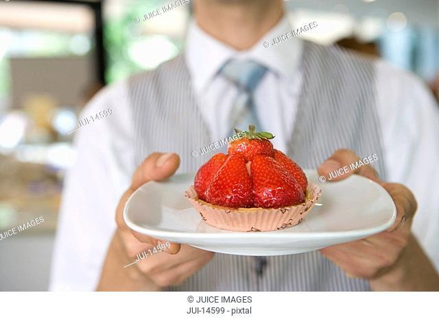 Waiter with strawberry tart, close-up of tart