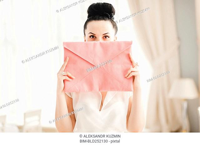 Glamorous Middle Eastern woman covering face with pink purse
